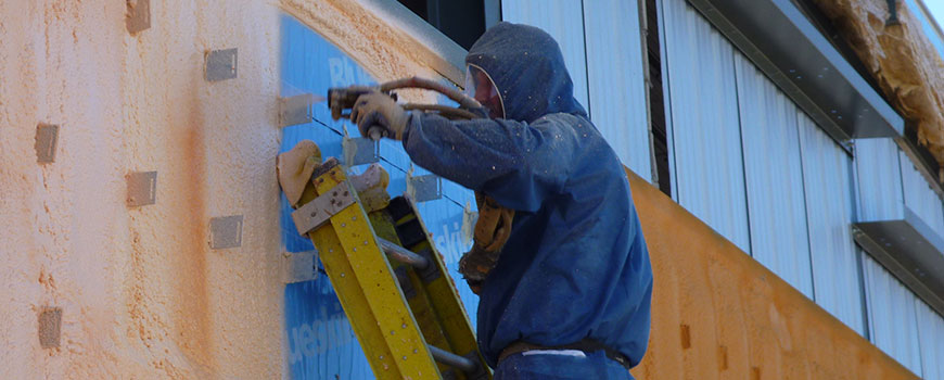 An Air Barrier Insulation employee spray foaming a school